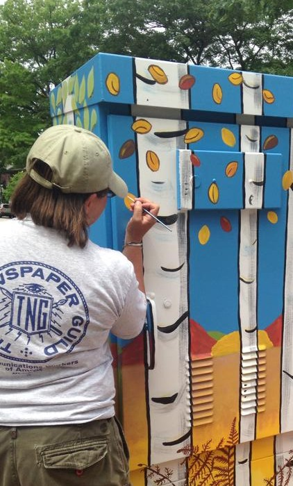 """Nancy Welsh puts the finishing touches on her public art project, entitled, """"Reasons for Seasons."""""""