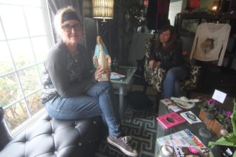 Kriss Blevens, left, with the Blessed Mother statue who watches over her new salon, sits with Sharon Curole, life celebrant and energy healer.