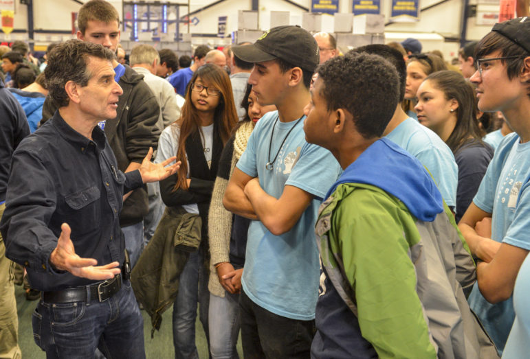 "FIRST® Founder Dean Kamen and FIRST Robotics Competition Team 1289, ""Gearheadz"" from Lawrence, Mass., talk excitedly at the Kickoff event in Manchester, New Hampshire – where more than 1,000 attendees gathered for the 2016 game reveal of FIRST STRONGHOLDSM."
