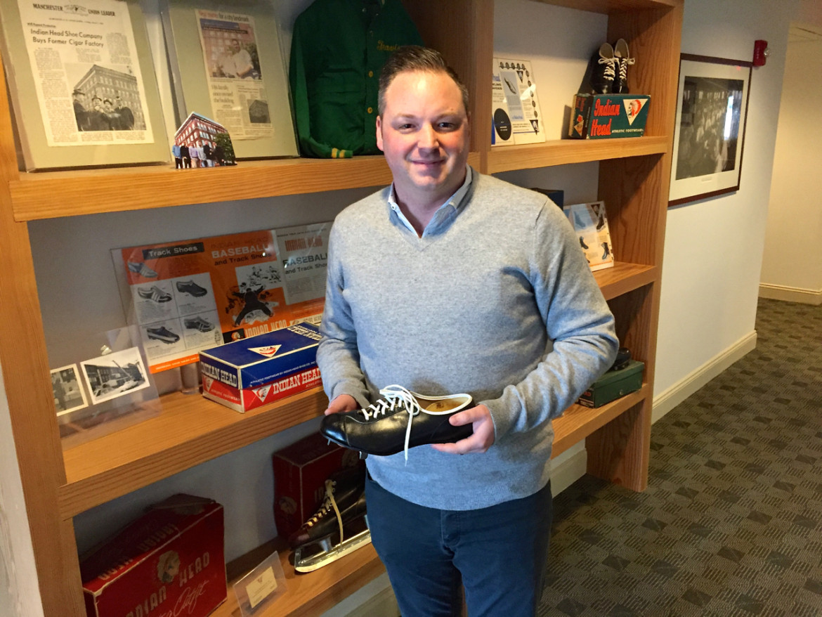 Travis York stands in front of a mini-museum of the family's 70 years in business. He's holding a cleat manufactured by the original Indian Head Athletic Company.