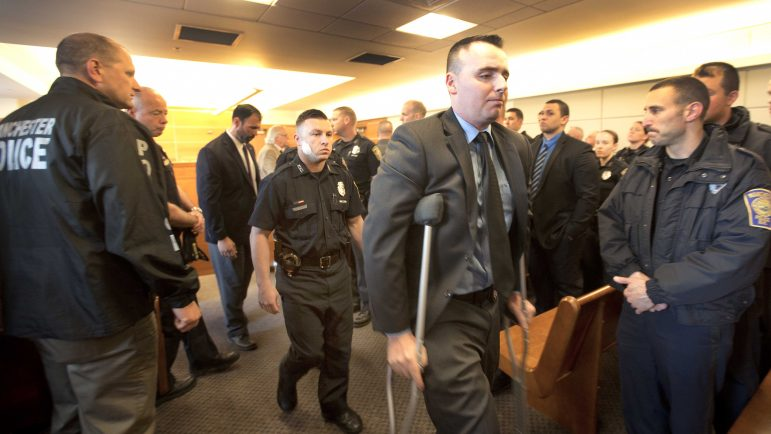 Mathew O'Connor, on crutches, and Ryan Hardy, behind him, leave the District Court Monday May 16, 2016 in Manchester, N.H. after the court hearing for Ian MacPherson, who was charged with shooting them last week. Ian MacPherson's lawyer entered not guilty pleas to two charges of attempted capital murder. (AP Photo/Jim Cole, Pool)