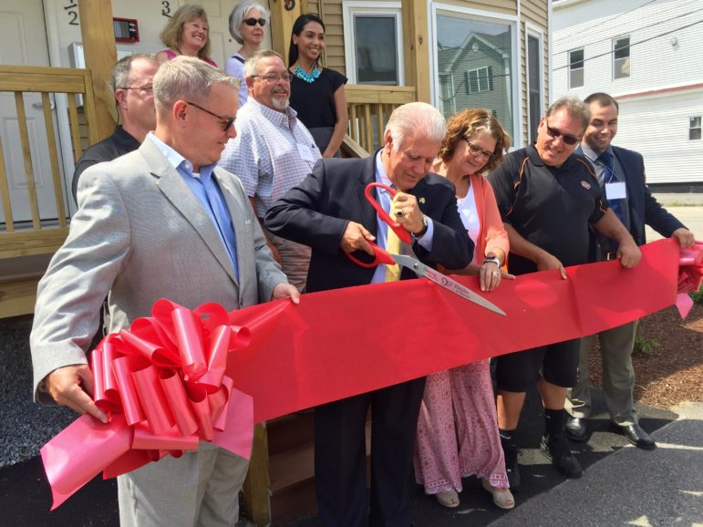 Mayor Ted Gatsas cuts the ceremonial ribbon on a refurbished apartment, the new home for four families, thanks to Families in Transition.