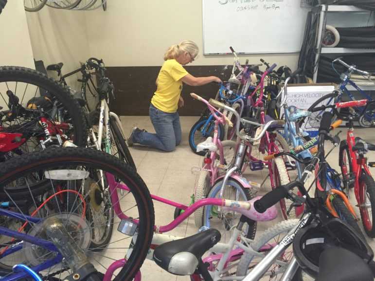 Abby Easterly checking out one of the many kids' bikes being repaired for resale.