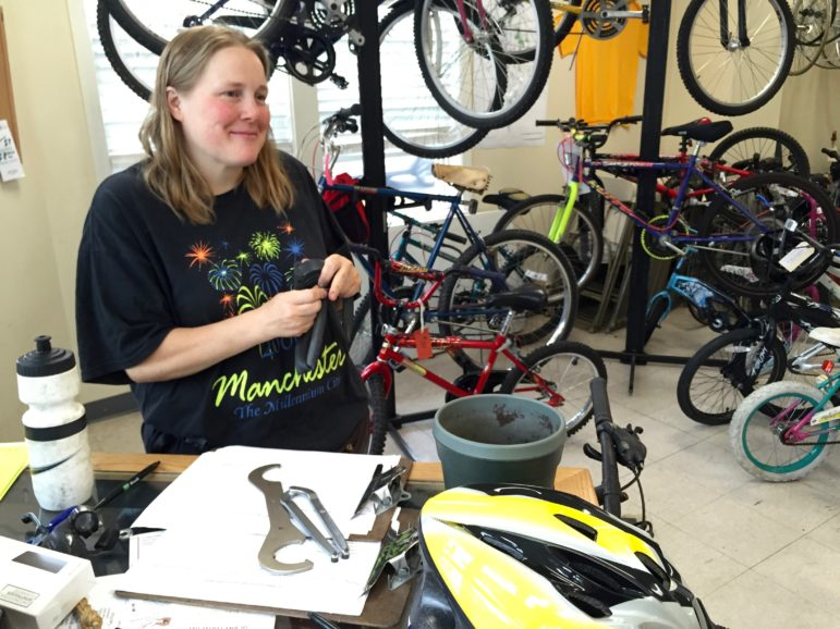 QC Bike Collective volunteer Sara Whiting checks some inner tubes for leaks.