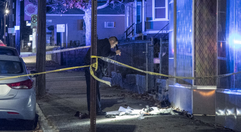 A police officer searches the sidewalk following a double shooting on the city's West Side early Saturday.