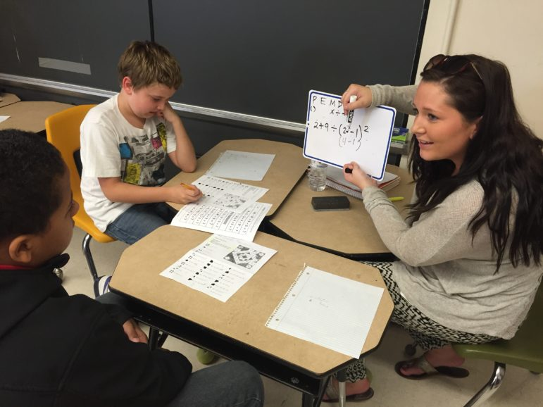 Hands on learning is a two-way street at Weston Elementary, as SNHU student Alivia Shea works with Andrew and Charles.