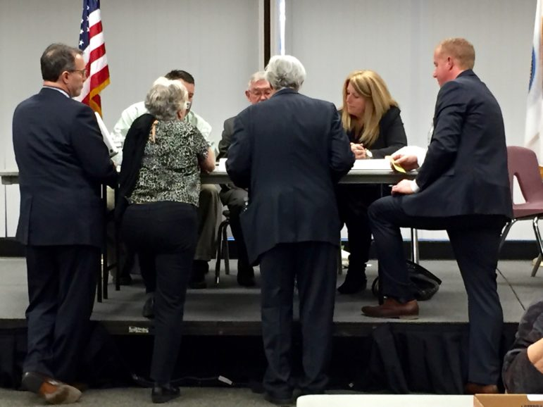 """Attorneys for the candidates confer with City Clerk Matthew Normand, right, and the three-member Recount Board after a """"glitch"""" was discovered in the Ward 1 ballot count."""