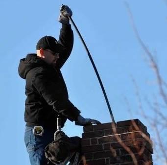John Ceaser of Ceaser Chimney Service LLC sweeping a chimney.