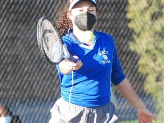 Helena Jackson hitting a tennis ball.
