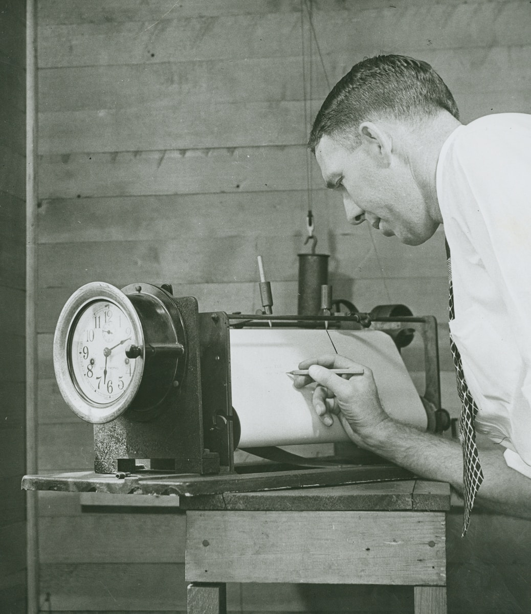 grayscale photo of man writing on paper