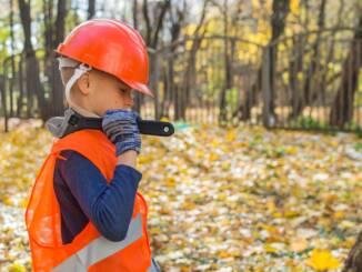 boy in orange and black jacket wearing red helmet holding black dslr camera